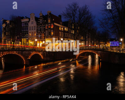 typical dutch scenery during blue hour with bridges canal and light trails from boats - Stock Photo