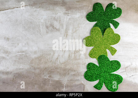 Three green shamrocks in a verticle line on right hand side.  Plenty of copy space. - Stock Photo