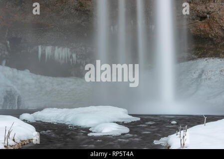 Detail of Seljalandsfoss in the winter, a unigue waterfall with a walking path behind it, Iceland - Stock Photo