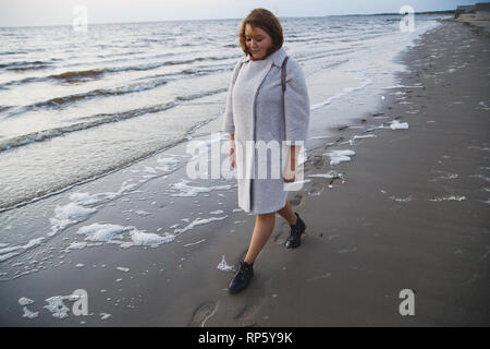 Alone girl in coat and leather boots walking along seashore. - Stock Photo