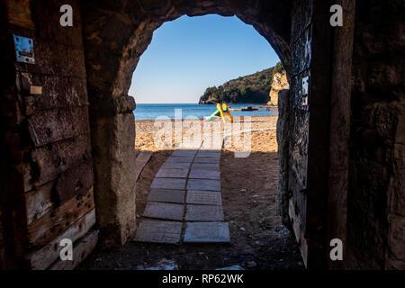 Ricardova Glava or Richard's Head beach on the Mediterranean coast. Accessible by an old medieval city gate. Budva, Montenegro - Stock Photo