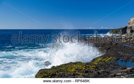 Waves crashing onto the rugged rocky coast of Koko Head, Koko Head District Park, Hawaii Kai, Oahu, Hawaii, USA - Stock Photo