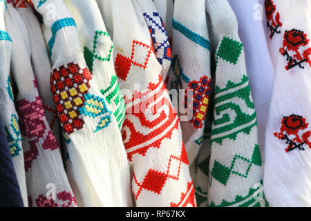 Colourful, tradtional clothes for sale on the market on Nicolae Balcescu Str, in Sibiu's old town, in Transylvania, Romania - Stock Photo