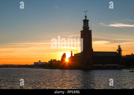Sunset behind the Stockholm Stadshus / town hall with sunrays, red sky and a blue waterfront as seen from Gamla Stan (Stockholm, Sweden, Europe) - Stock Photo