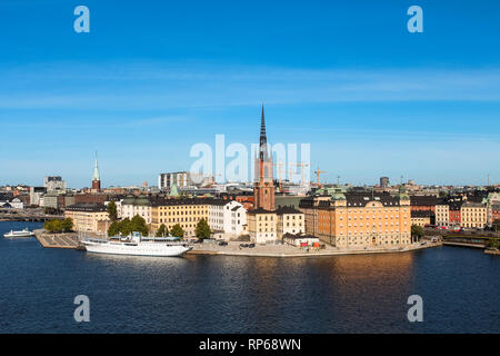 View onto Gamla Stan with Riddarholmskyrkan and a white large ship as seen from Södermalm during summer (Stockholm, Sweden, Europe) - Stock Photo