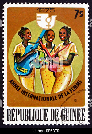 GUINEA - CIRCA 1976: a stamp printed in the Guinea shows Women Banjo and Guitar Players, International Womens Year 1975, circa 1976 - Stock Photo