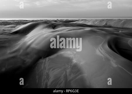 Untouched sand dunes at sunrise. Black and white image - Stock Photo