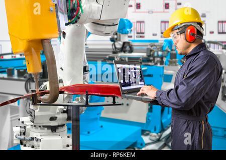 Engineer using laptop computer maintenance robot grip automotive workpiece position, Smart factory concept - Stock Photo