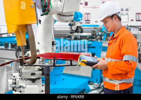 Engineer using laptop computer maintenance robot grip automotive workpiece, Industry 4.0 concept - Stock Photo