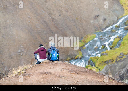Hveragerdi, Iceland - September 18, 2018: Reykjadalur during day in south golden circle landscape and young romantic couple people sitting on top of m - Stock Photo