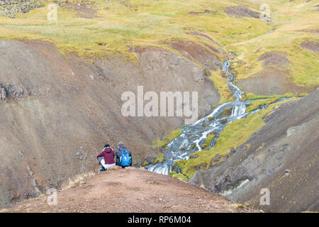 Hveragerdi, Iceland - September 18, 2018: Reykjadalur in south golden circle landscape and young romantic couple people sitting on top of mountain hik - Stock Photo