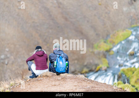 Hveragerdi, Iceland - September 18, 2018: Reykjadalur in south golden circle landscape and closeup young romantic couple people sitting on top of moun - Stock Photo