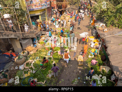 Aerial view over part of the Mullick Ghat Flower Market on a sunny day with crowds of local people sellers and buyers. - Stock Photo