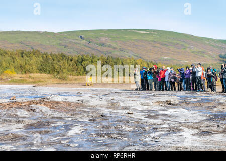 Haukadalur Valley, Iceland - September 19, 2018: Geyser landscape with people tourists waiting in south Icelandic country by Strokkur Geysir Hot Sprin - Stock Photo