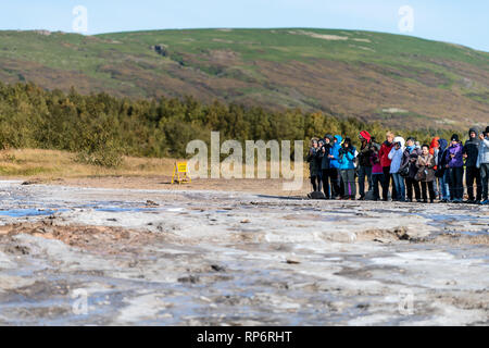 Haukadalur Valley, Iceland - September 19, 2018: Geyser landscape with people group waiting in south Icelandic country by Strokkur Geysir Hot Springs  - Stock Photo