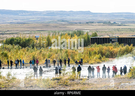 Haukadalur Valley, Iceland - September 19, 2018: Geyser landscape with people tourists waiting by Strokkur Geysir Hot Springs eruption on Golden Circl - Stock Photo