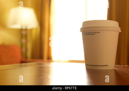 Cup of coffee to go at early morning in hotel room - Stock Photo