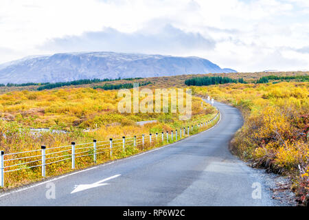 Landscape view of Thingvellir mountains on golden circle in Iceland during day and small road entrance to park for passing one way in autumn with nobo - Stock Photo