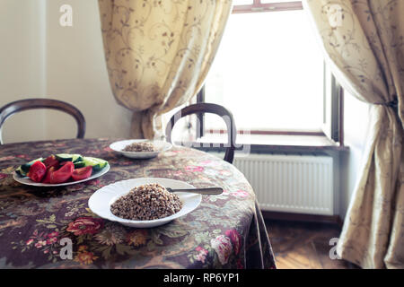 Rustic vintage wooden antique table tablecloth and window in Ukraine or Russia with plates of sliced vegetables cucumbers and tomatoes and cooked roas - Stock Photo