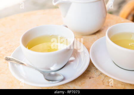 Closeup of two white cups on plates saucers of green or oolong tea in breakfast brunch outdoor cafe restaurant outside table with teapot pot - Stock Photo