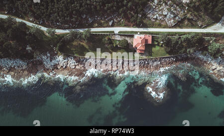 Drone aerial view of remote residential house on rocky beach in Galicia on a sunny bright day. - Stock Photo