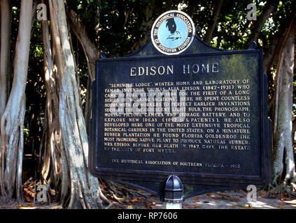 Amid the trunks of old banyan trees, a vintage sign describes the 1880s winter home and laboratory of renowned inventor Thomas Alva Edison in Fort Myers, Florida, USA. Those structures are now part of a sprawling historical museum where tourists can view and learn about some of Edison's most famous inventions, including the incandescent light bulb, phonograph, motion picture camera and storage battery. Edison's friend, automaker Henry Ford, purchased an adjoining home in 1916 and today it is part of the 21-acre Edison and Ford Winter Estates that include vast botanical gardens. - Stock Photo