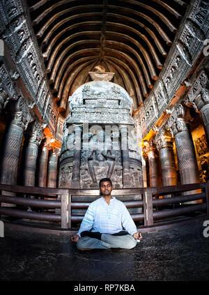 Indian Man doing meditation in lotus pose near the statue in ancient Ajanta cave near Aurangabad, Maharashtra, India - Stock Photo