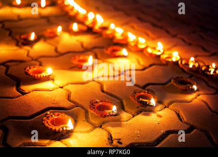 Traditional clay diya lamps lit on the ground during festival diwali celebration - Stock Photo