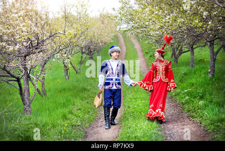 Couple in Kazakh costume walking around Spring Blooming apple garden of Almaty, Kazakhstan, Central Asia - Stock Photo