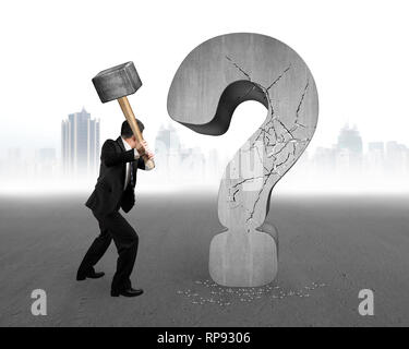 businessman holding hammer cracked question mark with gray cityscape concrete floor background - Stock Photo