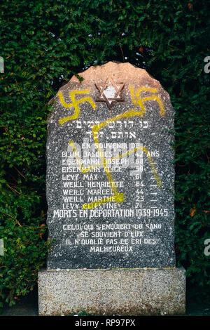 Vandalised rememberance monument stone with nazi symbols in yellow spray-painted on the damaged graves - Jewish cemetery in Quatzenheim near Strasbourg  - Stock Photo