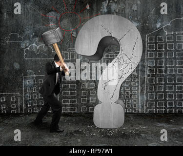 businessman holding hammer cracked question mark with city buildings doodles wall background - Stock Photo