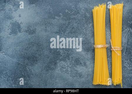 Raw macaroni, spaghetti on a dark stone table with copy space. Homemade Italian pasta - Stock Photo