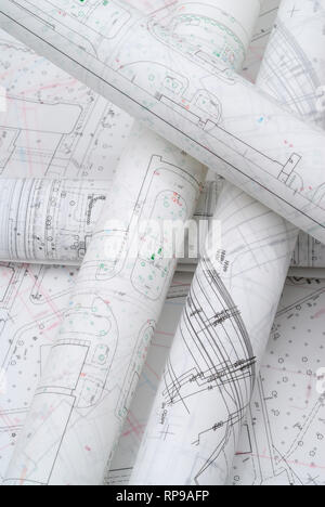 Rolled architectural plans lying on drawing board - Stock Photo