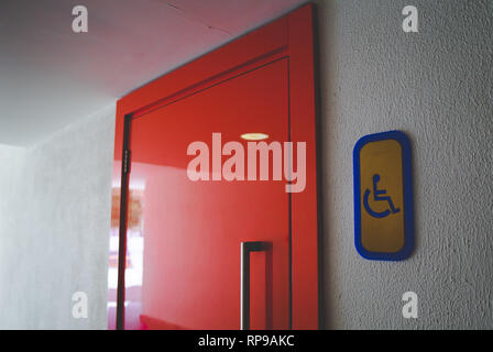 An entrance to the toilet for the disabled. Badge. View of a red toilet door with disabled sign on the right from the side. - Stock Photo