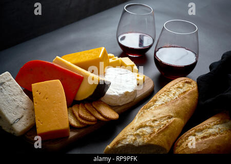 Wooden board with various types of cheese and baguette and two glasses of red wine on black smooth table - Stock Photo