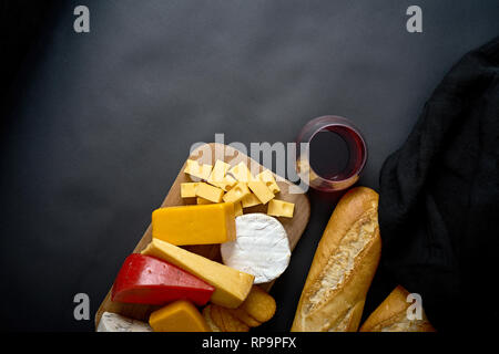 Wooden board with various types of cheese and baguette and glass of red wine on black smooth table - Stock Photo