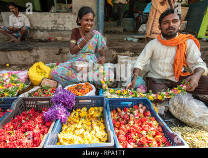 A trader seller of flowers smiling and posing for the camera at the busy Madurai flower market in India. - Stock Photo