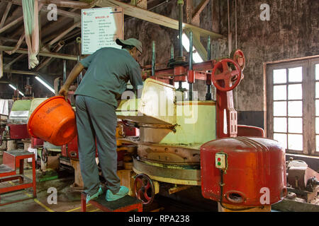 Worker at work in the Lockhart tea factory using traditional methods and machinery.  This is the drying process. - Stock Photo