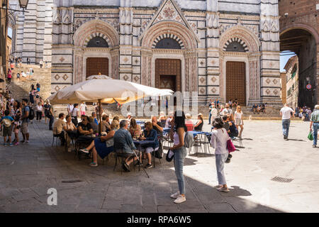 People at pavement cafe close to Duomo di Siena (Siena Cathedral), Tuscany, Italy - Stock Photo