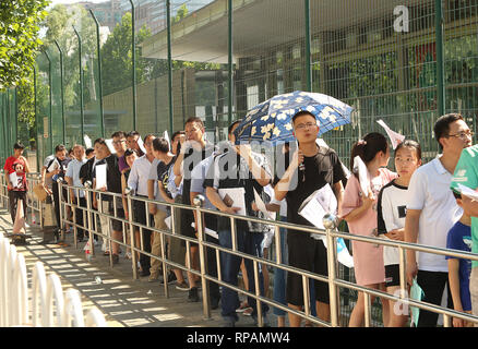 July 26, 2018 - Beijing, China - Chinese wait in line to apply for a visa outside the U.S. Embassy after a small 'bomb' was set-off in the intersection near the embassy in Beijing on July 26, 2018.  A 26-year-old man from Inner Mongolia detonated a small explosive on the street, police said, injuring himself before being taken into custody.  News of the incident was quickly censored on Chinese social media. . (Credit Image: © Todd Lee/ZUMAprilESS.com/ZUMA Wire) - Stock Photo