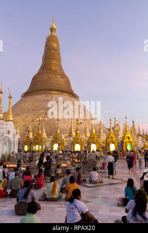 Worshippers sitting on the floor in front of the golden dome of shwedagon Pagoda at dusk. Lit candles illuminate stupas that house a Buddha statue. - Stock Photo