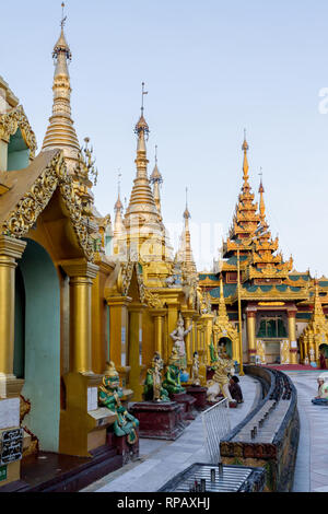 Worshippers sitting on the floor in front of Buddhist stupas each housing a Buddha statue. - Stock Photo