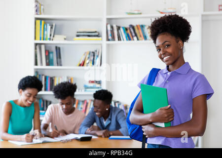 Beautiful african american female student at classroom of university - Stock Photo