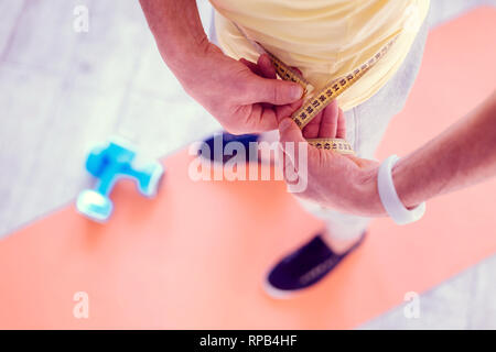Man wearing white smart watch on his hand measuring his waistline - Stock Photo