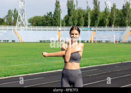 young female athlete stretching and warming up on run track in stadium sport and fitness concept. - Stock Photo