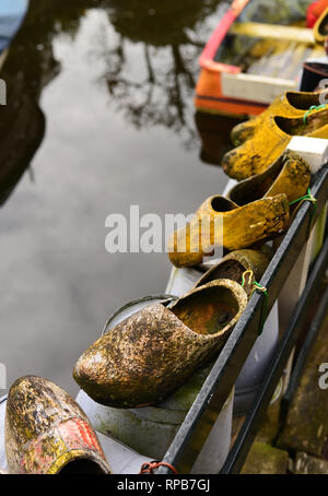 Traditional dutch wooden shoes hanging over a water channel. Holland The Netherlands - Stock Photo