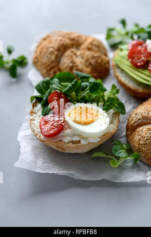 Bagel sandwiches with cream cheese, avocado, tomatoes, egg and greens on gray wooden background. Selective focus. Healthy eating or vegetarian food co - Stock Photo