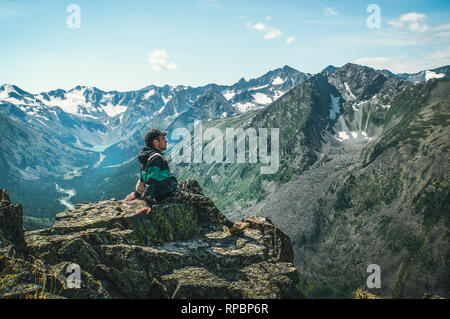 Man sit on sharp cliff above valley in rocky mountains park and watch into landscape. The tourist has conquered the top of the mountain and sits enjoy - Stock Photo