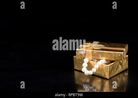 Golden jewellery box with shiny pearls on a black glossy background - Stock Photo